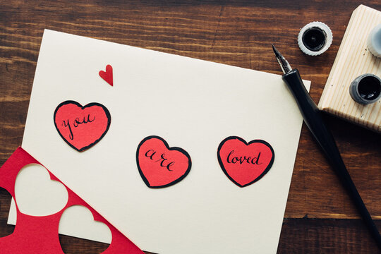 """You are loved"""""""" message written on red paper hearts with ink pen"""