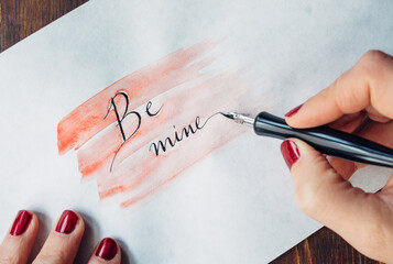 """Woman's hand writing """"""""Be Mine"""""""" on paper"""