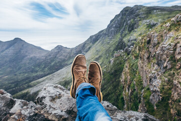 leather shoes and jeans of a hiker sitting on a mountain top