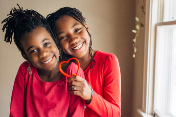 Cute African American girls in red holding a heart shaped cookie cutter