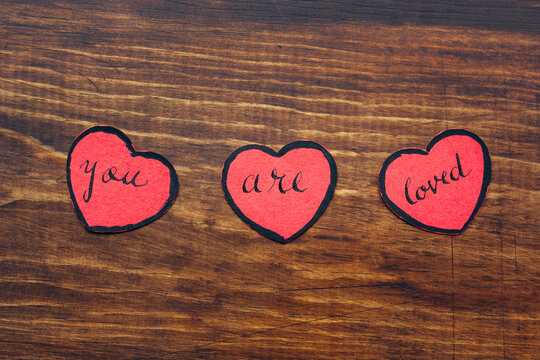 """Three red paper hearts with the message """"""""you are loved"""""""""""