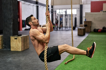 Man climbing a rope in a gym
