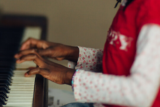 Hands of a black girl playing the piano