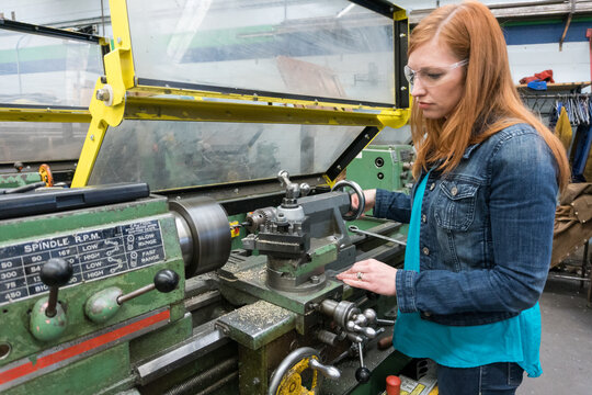 Female company executive tries out lathe in machine shop