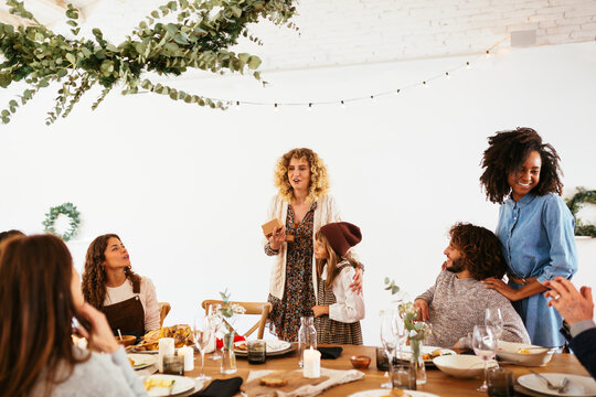 Woman with girl giving speech during family party
