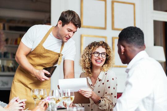 Waiter helping diverse friends to make order