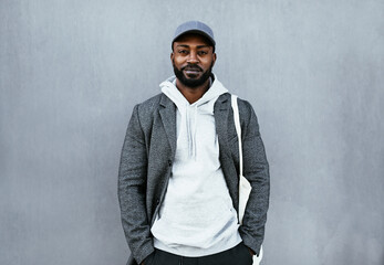 Relaxed black man against gray wall