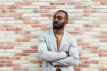 Confident black man near brick wall