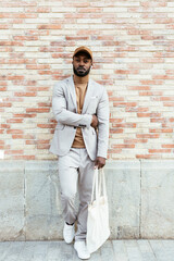 Stylish black guy listening to music near brick wall