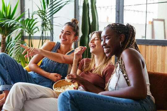Cheerful diverse teenagers watching comedy at home