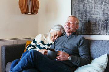 Senior couple laughing and watching TV together