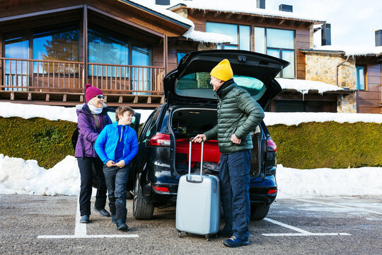 Grandparents and grandson on parking lot on winter day on resort