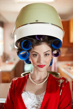 Portrait of contemporary woman sitting under a vintage hair dryer in a mid-century modern environment.
