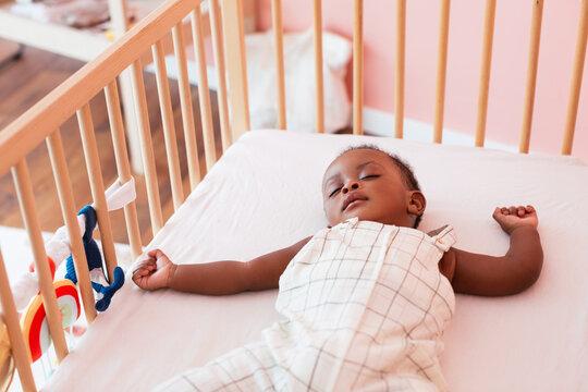 Black baby sleeping in crib
