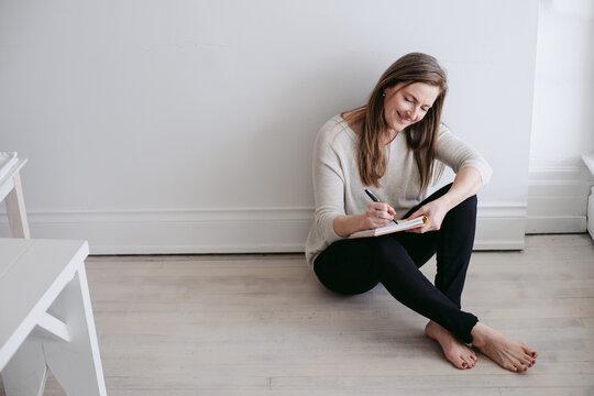 Mature woman sitting on floor enjoying tea or coffee and journaling