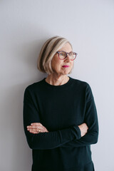 Portrait of mature woman wearing glasses on seamless white studio background