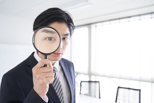 会議室で虫眼鏡を覗き込む日本人男性ビジネスマン