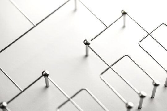 Hierarchy, command chain, company / organization structure or layer and grouping concept image. Top down structure made from chrome wires and silver nails and wire on white. Shallow depth of field.