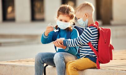 Schoolkids disinfecting hands during coronavirus pandemic.