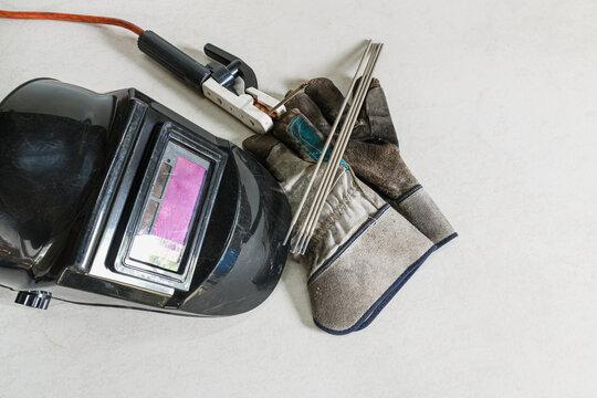 Welding equipment including leather welding gloves, welding mask, hand held welding electrode on  floor