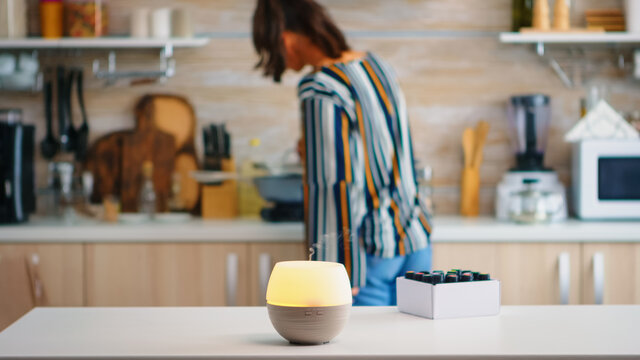 Essential oils diffuser distributing aromatherapy while woman walks in the kitchen. Aroma health essence, welness aromatherapy home spa fragrance tranquil theraphy, therapeutic steam, mental health