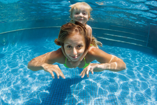 Happy family - young mother, baby boy learn to swim, dive underwater. Jump with fun in swimming pool. Healthy lifestyle, active parents, people water sports activities on summer holidays with kids.