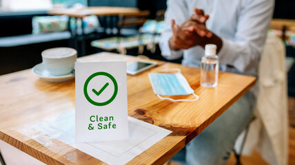 Clean and safe sign with unrecognizable man disinfecting his hands with hydroalcoholic gel in background