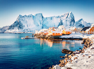 Sunny morning scene of popular tourist destination - Lofoten Islands archipelago. Colorful houses on the shore of Norwegian sea. Winter view of Sakrisoy fishing village.  Life over polar circle.