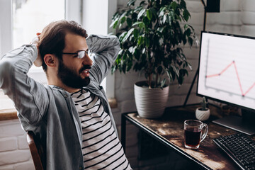 Focused young businessman in eyewear checks graphics on computer monitors. Concentrated millennial man in glasses works at home on self-isolation