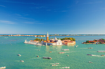 Papiers peints Gondoles Aerial panoramic view of San Giorgio Maggiore island with Campanile San Giorgio in Venetian Lagoon, sailing boats in Giudecca Canal, Lido island, blue sky background, Venice city, Veneto Region, Italy
