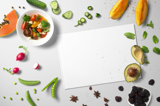 Top view kitchen counter with avo, papaya, radishes, berries, mango and a bowl of salad with a blank piece of paper