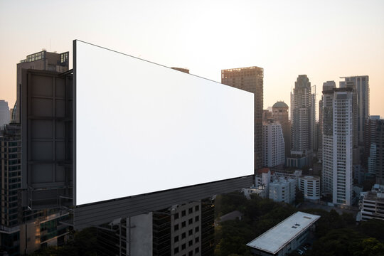 Blank white road billboard with Bangkok cityscape background at sunset. Street advertising poster, mock up, 3D rendering. Side view. The concept of marketing communication to promote or sell idea.