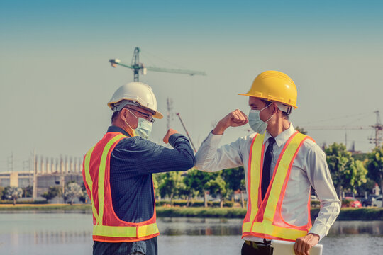 Engineers saluting each other by touching elbows,Two business people shake hand no touch outdoor on site construction