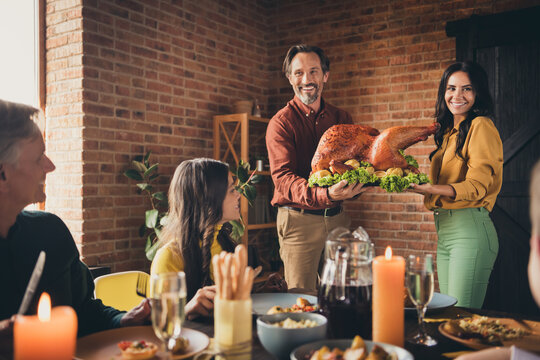 Portrait of nice attractive cheerful big full family meeting wife husband married couple carrying plate fresh homemade turkey serving table occasion at modern loft industrial brick interior house