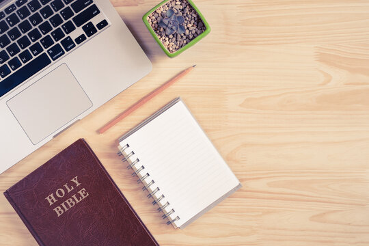 Top view of Holy Bible, laptop, notebook, and pencil on wooden background