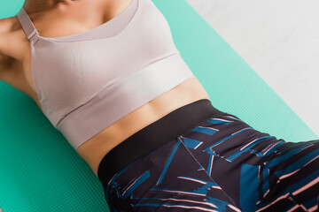 Cropped view of fit woman in sportswear lying on fitness mat