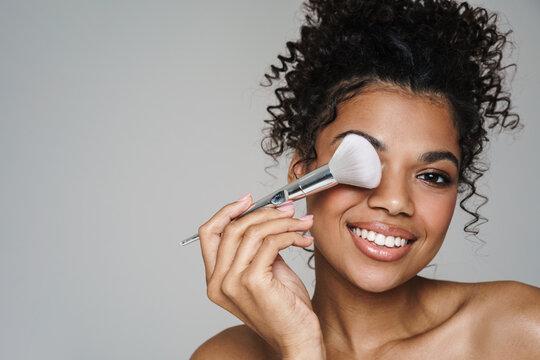 Image of shirtless african american woman using powder brush and smiling