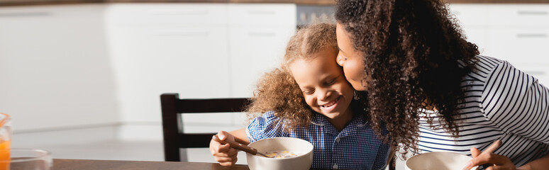 horizontal image of african american woman kissing daughter during breakfast