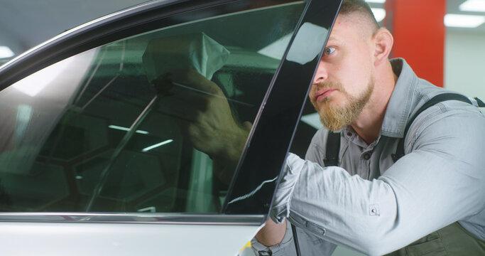 Bearded mechanic spraying tinted window
