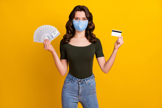 Portrait of her she attractive wavy-haired girl wear safety reusable mask holding hand bank card fan cash mers cov prevention insurance isolated bright vivid shine vibrant yellow color background