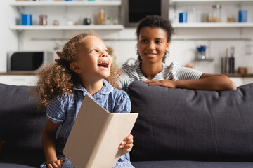 selective focus of african american babysitter behind excited girl holding open book while sitting...