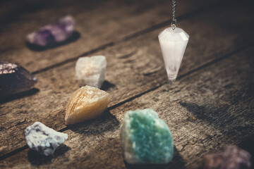 Crystal Pendulum with healing gemstones on wooden table, spirituality and esoteric