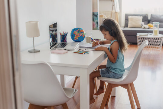 Little girl doing home school over the internet due to COVID-19 pandemic