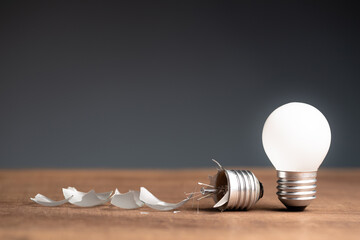 Glowing small light bulb and the broken one on the table, concept of fail and success, bad and good idea, problem and solution, learning from mistake or pros and cons object