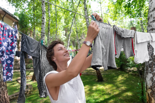 Candid real life portrait of young adult beautiful attractive caucasian woman hanging up fresh washed family clothes on birch tree clothesline with pins at home yard on bright sunny day outdoors