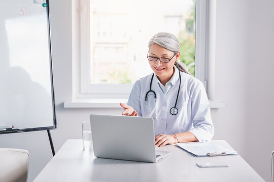 Telemedicine concept. Senior female doctor talking with patient using laptop online video webinar consultation while sitting in clinic office.