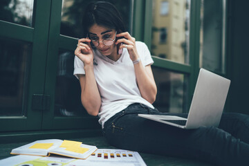 Amazed female student in classic glasses shocked with noted information in education textbook, wonder freelancer with modern laptop computer calling to partner for discussing project planning