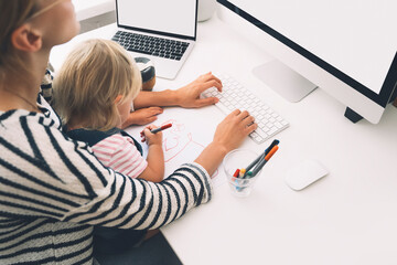 Mother working from home with little child.