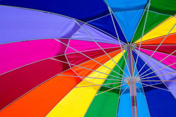 Closeup image of a rainbow coloured umbrella