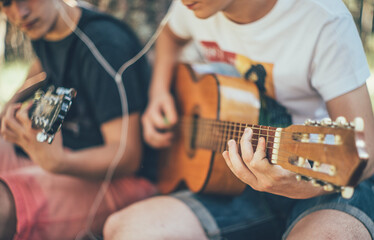 Two teenage boys playing the guitar while listening to music.